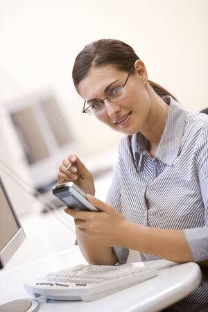Woman in computer room using personal digital assistant and smiling photo
