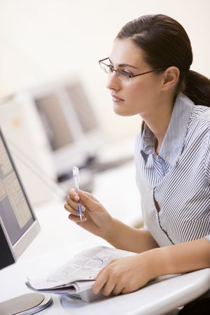 Woman in computer room circling items in a newspaper Stock Photo - 3460871