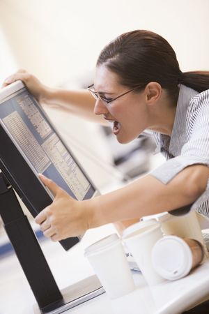 Woman in computer room grabbing her monitor and screaming Stock Photo - 3458958