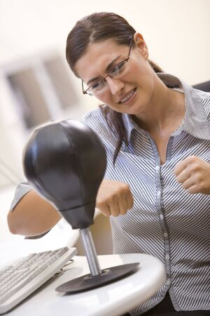 Woman in  room using small punching bag for stress relief Stock Photo - 3472719