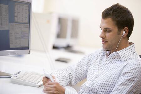 Man in computer room listening to MP3 player photo