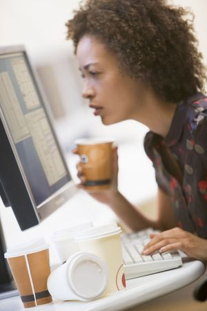 Woman in computer room with many cups of empty coffee around her photo