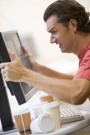 addiction: Man in computer room with many empty cups of coffee grabbing his monitor frustrated