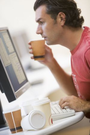 Man in computer room with many empty cups of coffee photo