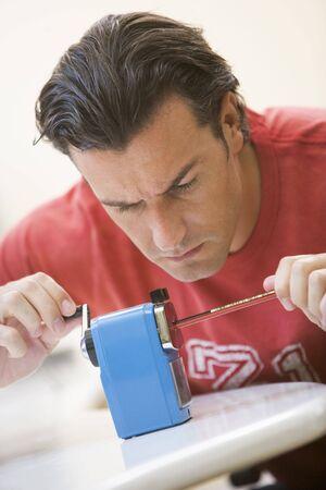 sharpener: Man indoors using pencil sharpener