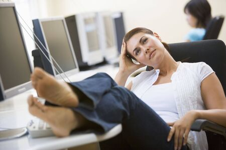 barefeet: Woman in computer room with feet up thinking Stock Photo