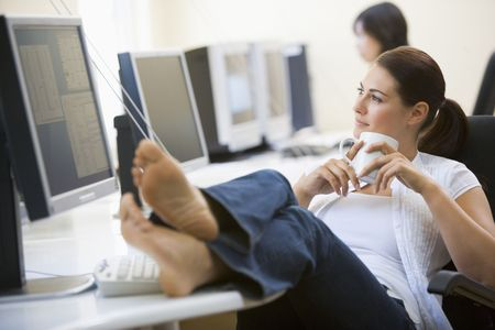 Woman in computer room with feet up drinking coffee
