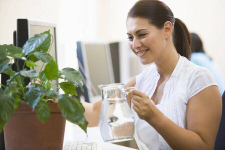 office break: Mujer en sala de ordenadores de riego de plantas sonriente