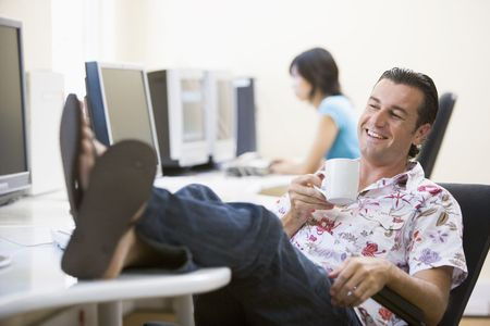 Man in computer room with feet up drinking coffee and smiling photo