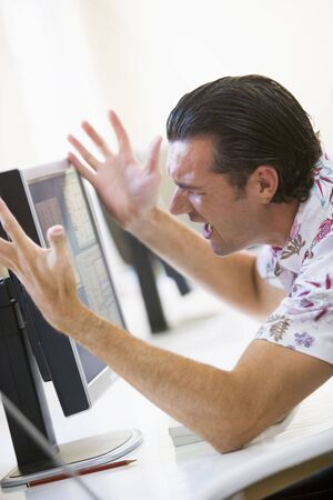 Man in computer room frustrated at monitor Stock Photo - 3460804