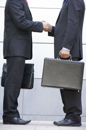 Two businessmen holding briefcases outdoors shaking hands photo