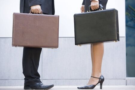 Two businesspeople holding briefcases outdoors photo