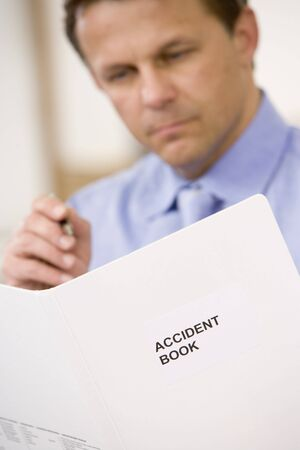 Businessman indoors looking at Accident Book photo