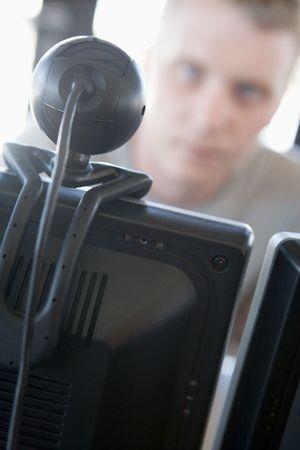 Shot of a man behind a computer and web camera