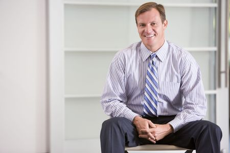 Businessman sitting indoors smiling photo
