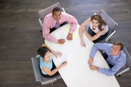 collaborating together: Four businesspeople at boardroom table smiling