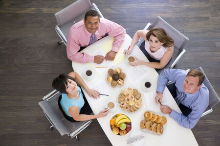 Four businesspeople at boardroom table with breakfast smiling photo