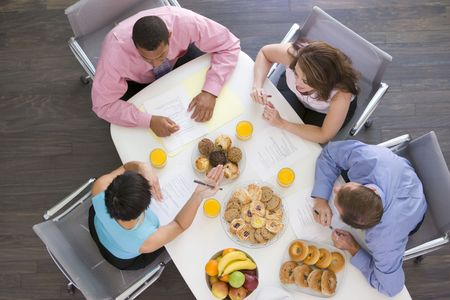 Four businesspeople at boardroom table with breakfast photo