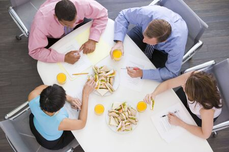 Four businesspeople at boardroom table with sandwiches photo