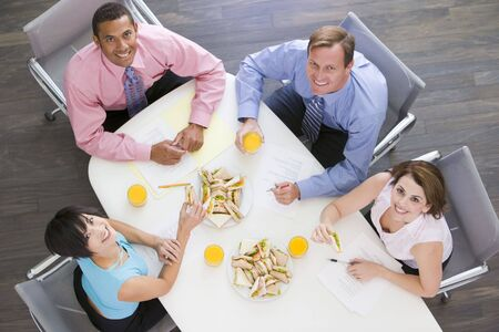 Four businesspeople at boardroom table with sandwiches smiling Фото со стока