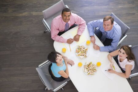Four businesspeople at boardroom table with sandwiches smiling photo