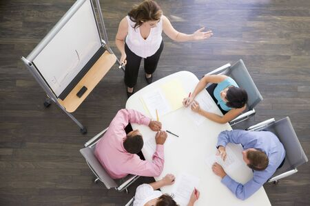 flipchart: Four businesspeople at boardroom table watching presentation Stock Photo