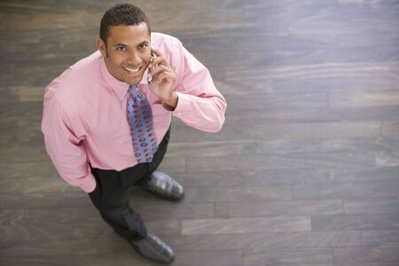 Businessman standing indoors using cellular phone smiling photo