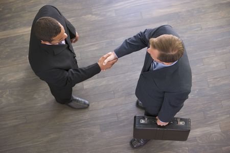 overhead view: Two businessmen indoors shaking hands Stock Photo