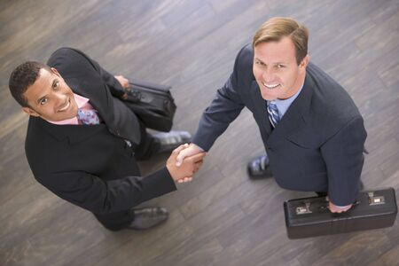 Two businessmen indoors shaking hands smiling photo