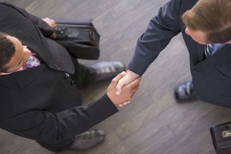 Two businessmen indoors shaking hands photo