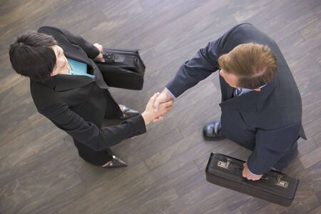 Two businesspeople indoors shaking hands photo