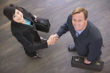 Two businesspeople indoors shaking hands smiling photo