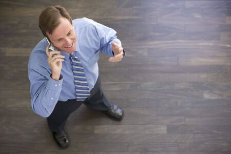 working week: Businessman standing indoors using cellular phone and smiling