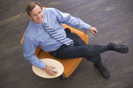 working week: Businessman sitting indoors with cellular phone smiling