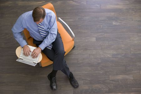 working week: Businessman sitting indoors with laptop Stock Photo