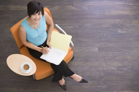 Businesswoman sitting indoors with coffee and folder smiling photo