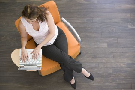 Businesswoman sitting indoors with laptop photo
