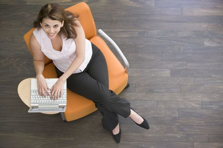 working week: Businesswoman sitting indoors with laptop smiling