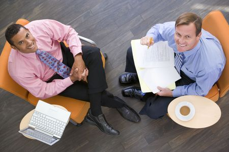 Two businessmen sitting indoors with coffee laptop and folder smiling photo