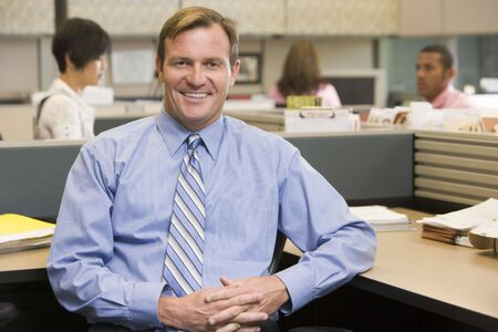 Businessman in cubicle smiling photo