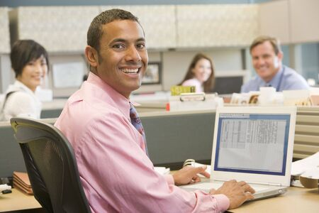 working week: Businessman in cubicle using laptop and smiling