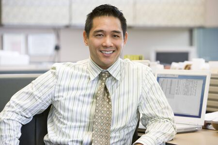 Businessman in cubicle smiling Stock Photo - 3461126