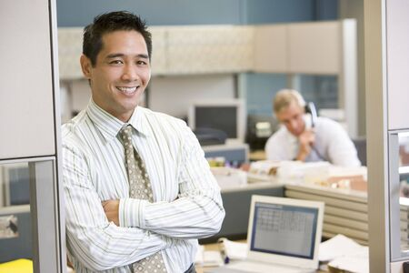 Businessman standing in cubicle smiling photo