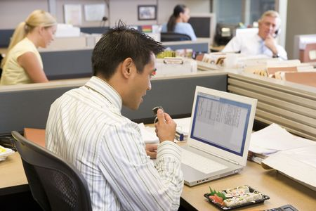 Businessman in cubicle at laptop eating sushi photo