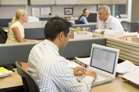 open plan office: Businessman in cubicle at laptop