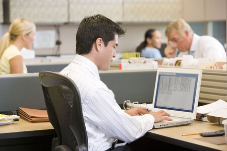 Businessman in cubicle using laptop photo