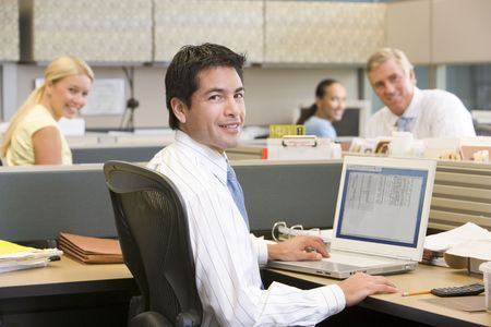 Businessman in cubicle with laptop smiling photo