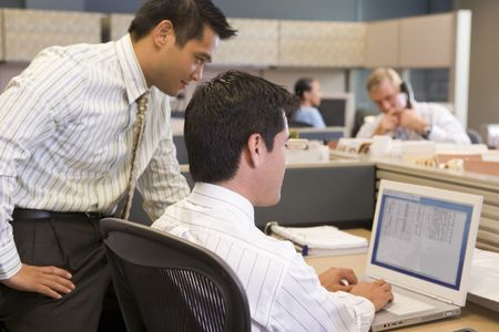 Two businessmen in cubicle looking at laptop photo