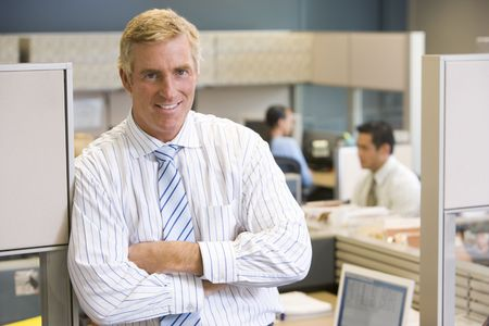 Businessman standing in cubicle smiling Stock Photo - 3470972