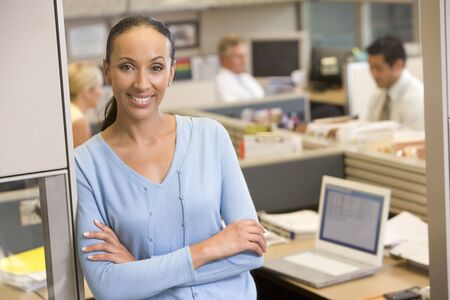 Businesswoman standing in cubicle smiling photo